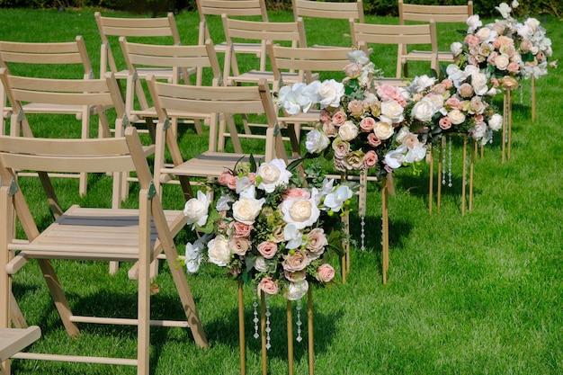 Cadeiras vazias de madeira brancas em seguido e ramalhetes das flores na grama verde. decorações de cerimônia de casamento.