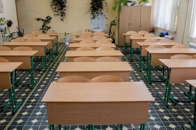 Cadeiras velhas da linha de madeira palestra em sala de aula na escola pobre