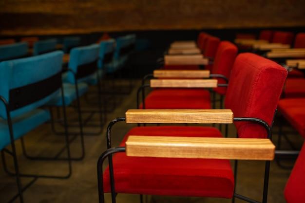 Cadeiras vermelhas e azuis no corredor escuro de um pequeno cinema