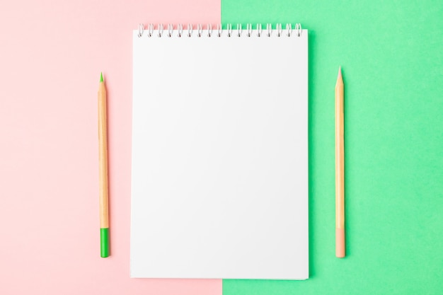 Caderno aberto branco em fundos verdes e cor-de-rosa. nas proximidades existem lápis.
