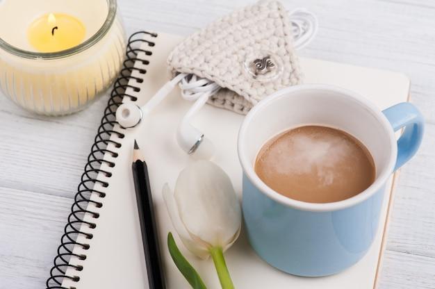 Caderno aberto, café, vela, earpods e tulipa