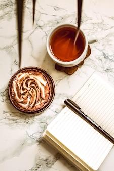 Caderno aberto com área vazia, pena e um copo do chá preto em uma tabela de mármore branca no tempo de manhã.