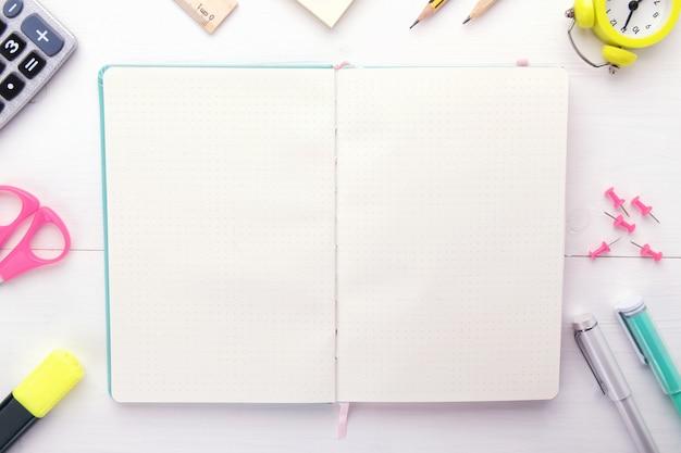 Caderno aberto com artigos de papelaria