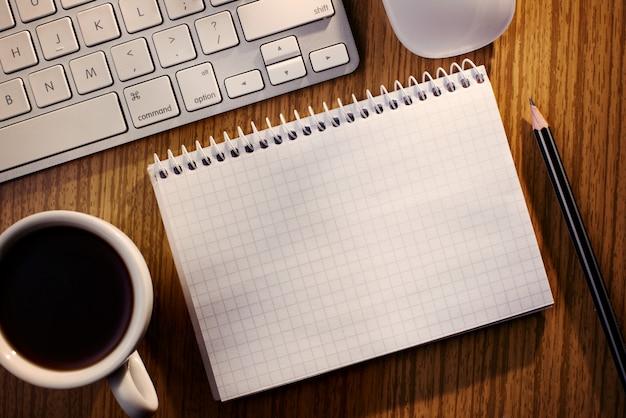 Caderno aberto com café ao lado de um teclado