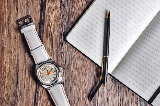 Caderno aberto com caneta e relógio de pulso