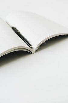 Caderno aberto com caneta na superfície branca