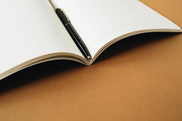 Caderno aberto com caneta na superfície laranja gengibre