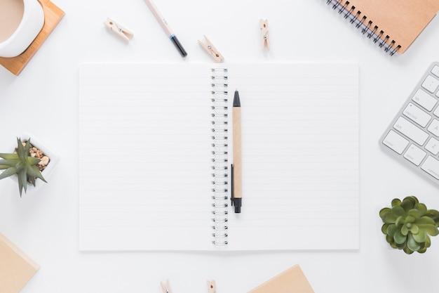 Caderno aberto com caneta perto de artigos de papelaria