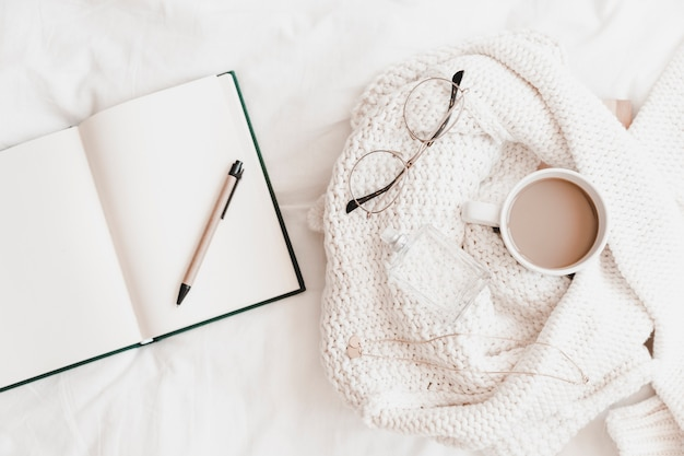 Caderno aberto com caneta perto de camisola com coisas no lençol