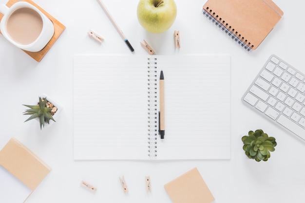 Caderno aberto com caneta perto de papelaria e maçã na mesa branca