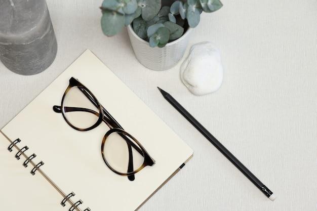 Caderno aberto com caneta preta, planta verde, pedra e vela