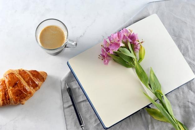 Caderno aberto com flores alvas e café preto