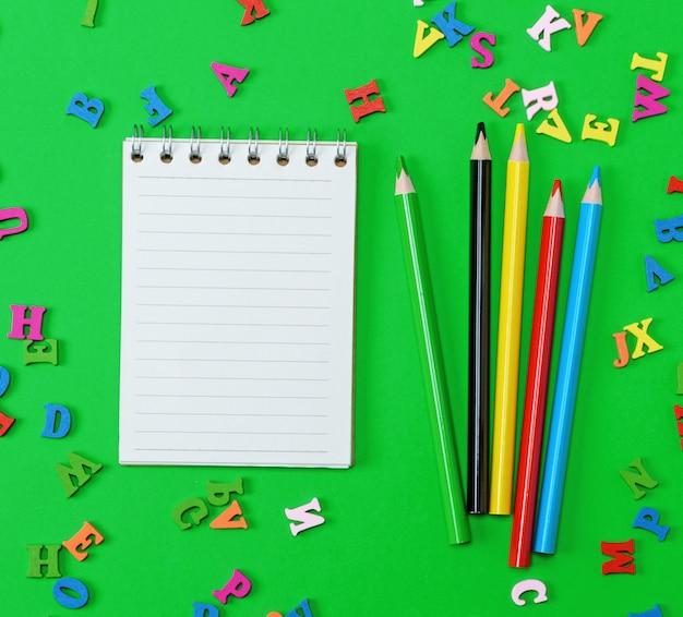 Caderno aberto com folhas brancas em branco na linha, lápis de madeira coloridos