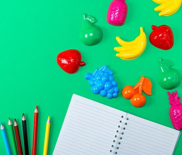 Caderno aberto com folhas brancas vazias e lápis de madeira multicoloridos