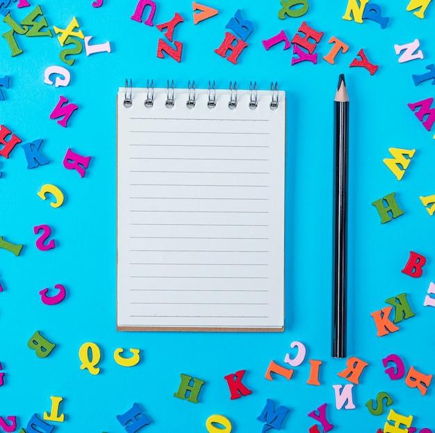 Caderno aberto com folhas brancas vazias e lápis preto
