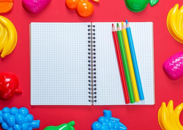 Caderno aberto com folhas brancas vazias em uma célula e lápis de madeira multicoloridos