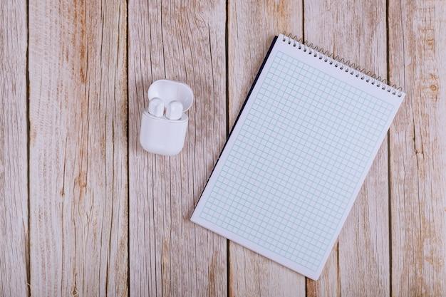 Caderno aberto com fones de ouvido sem fio na mesa de madeira