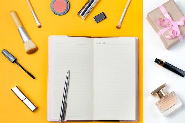 Caderno aberto com itens de maquiagem, perfume e caixa de presente