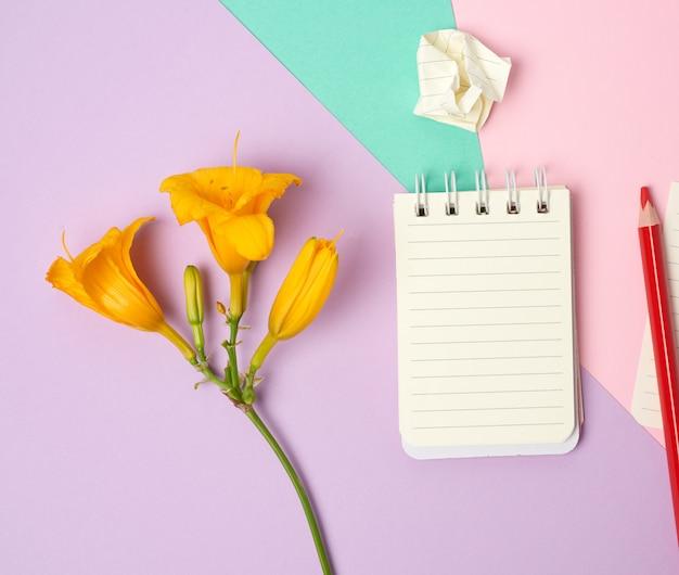 Caderno aberto com lençóis brancos e flor amarela em um espaço roxo