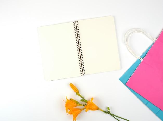 Caderno aberto com lençóis brancos em branco e sacolas de papel multicoloridas