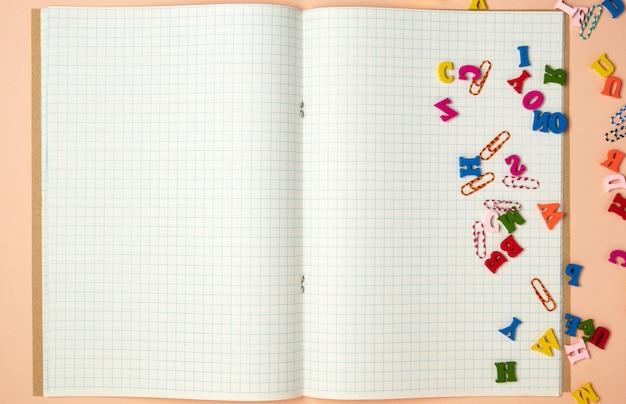 Caderno aberto com lençóis brancos em uma gaiola e pequenas letras de madeira coloridas