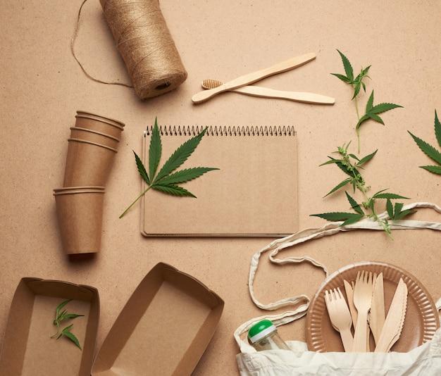 Caderno aberto com lençóis vazios, uma sacola têxtil e talheres descartáveis de papel artesanal marrom, folhas verdes de cânhamo