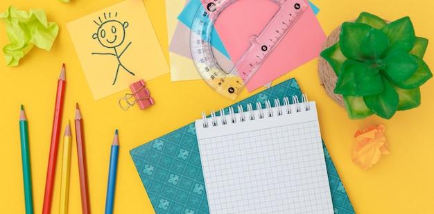 Caderno aberto com material escolar