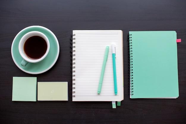 Caderno aberto com nota auto-adesiva e canetas papelaria na mesa cinza escura