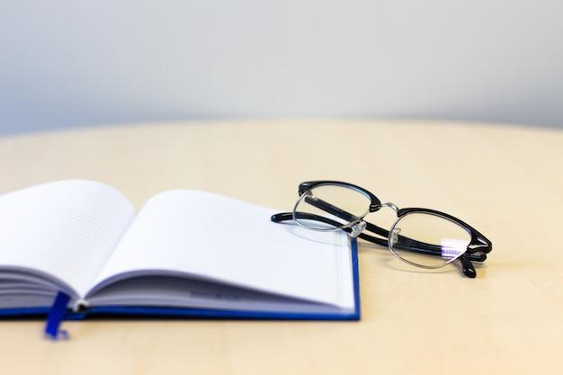 Caderno aberto com óculos na mesa de madeira, cópia espaço para texto.