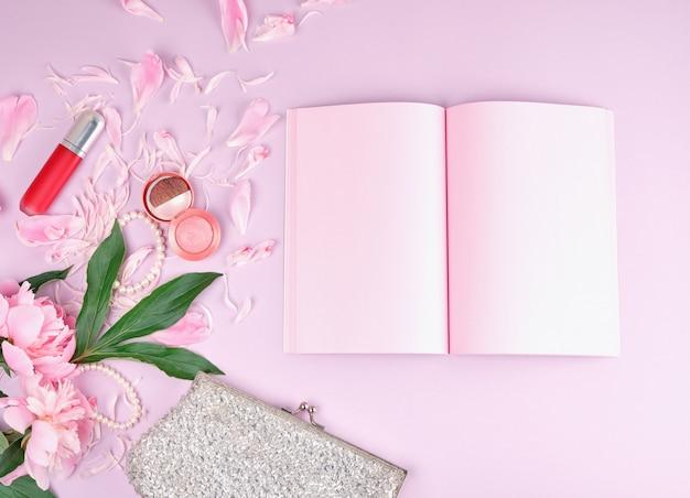 Caderno aberto com páginas cor de rosa em branco, buquê de peônias