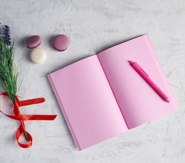 Caderno aberto com páginas cor de rosa em branco, lápis vermelho e um buquê de alfazemas
