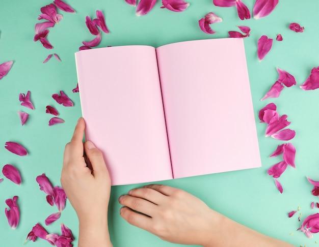 Caderno aberto com páginas cor de rosa vazias e duas mãos femininas
