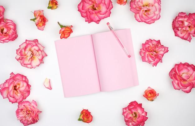 Caderno aberto com páginas em branco cor de rosa e pétalas de uma rosas cor de rosa
