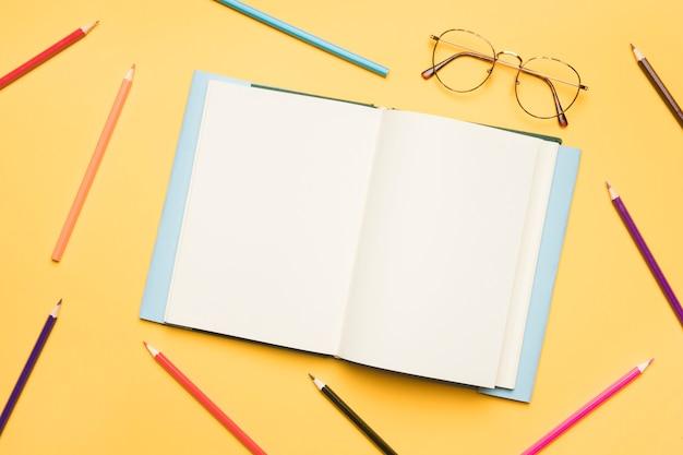 Caderno aberto com páginas em branco rodeado por lápis