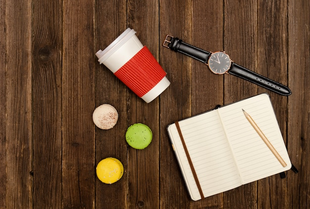 Caderno aberto com um lápis, biscoitos, copos de papel e um relógio