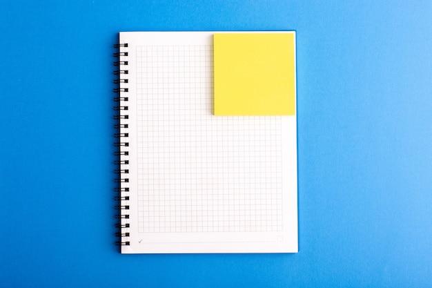 Caderno aberto de vista frontal com adesivo na superfície azul