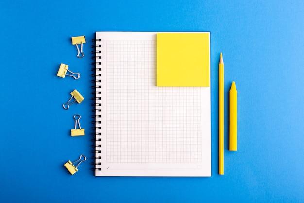 Caderno aberto de vista frontal com adesivos e lápis na superfície azul