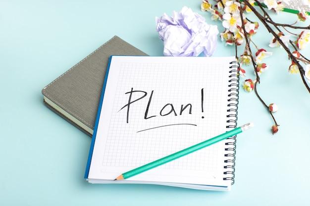 Caderno aberto de vista frontal com lápis e flores na superfície azul