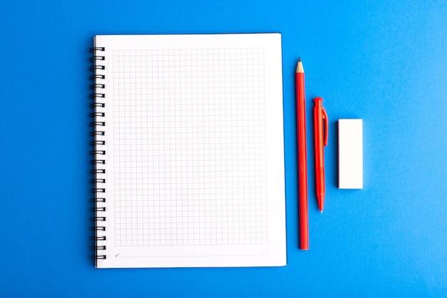 Caderno aberto de vista frontal com lápis na superfície azul