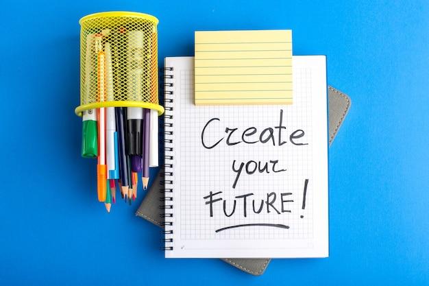 Caderno aberto de vista superior com canetas hidrográficas e lápis coloridos na superfície azul