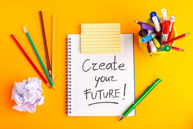 Caderno aberto de vista superior com lápis coloridos e canetas hidrográficas na superfície laranja