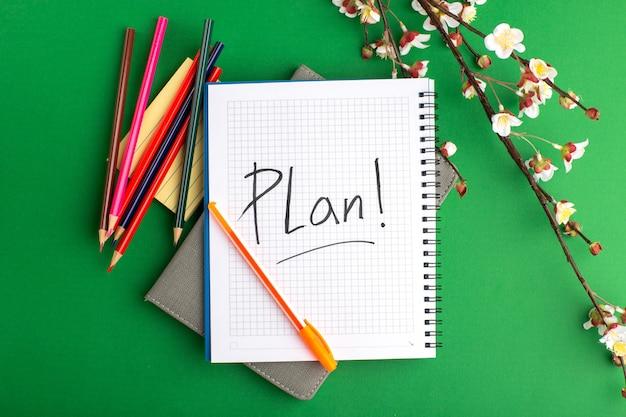 Caderno aberto de vista superior com lápis coloridos e flores na superfície verde