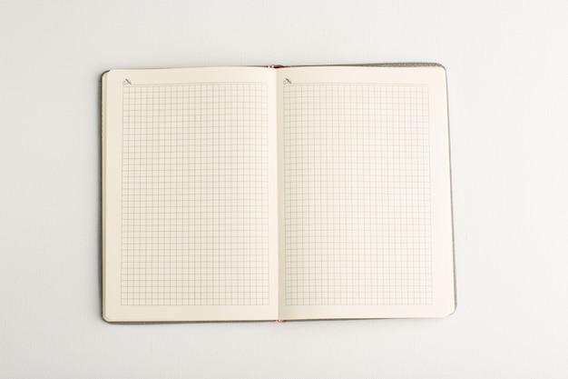 Caderno aberto de vista superior na superfície branca