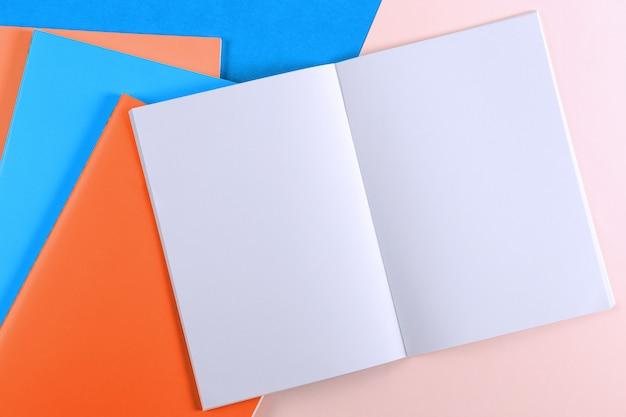 Caderno aberto e cadernos coloridos na mesa azul e rosa