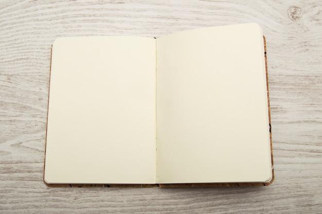 Caderno aberto e em branco na mesa de madeira
