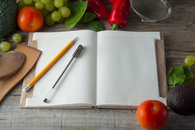 Caderno aberto e fundo de legumes frescos. conceito de dieta. copie o espaço.