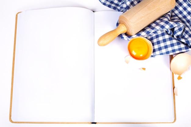 Caderno aberto e ingredientes básicos de panificação