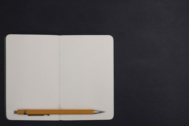 Caderno aberto e lápis sobre fundo preto