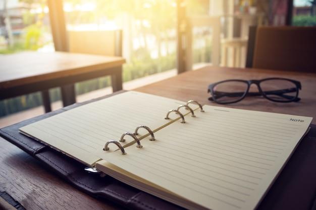 Caderno aberto e óculos em fundo de madeira