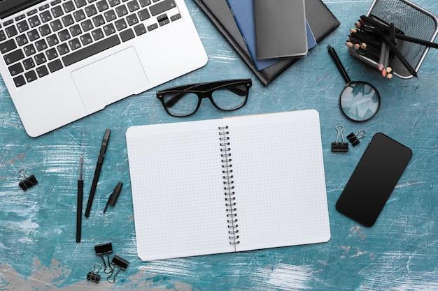 Caderno aberto e outro equipamento de escritório na mesa de escritório.